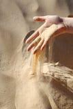 Sand slipping through fingers Stock Image