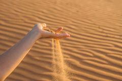 Sand slipping through the fingers of a woman's hand in the deser Stock Images