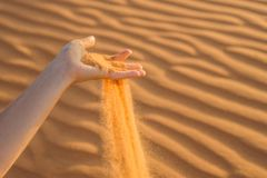 Sand slipping through the fingers of a woman's hand in the deser. T Stock Images
