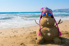 Sand snowman with hat on the beach. Snowman made of sand dressed as a snowboarder on the beach Royalty Free Stock Photo