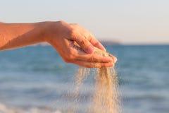 Sand som flödar till och med händer royaltyfria foton