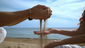 Sand som häller i människahänder på stranden wrist för watch för avkoppling för begreppshandfack arkivfilmer