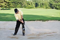 Sand Splash. Man hitting out of sand trap. Sand flying and ball visible in front of pant leg stock images