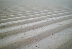 Sand steps left by the tide. A series of steps left in the sand by the receding tide. The sand is white. Small holes made by crabs can be seen. The steps Royalty Free Stock Images