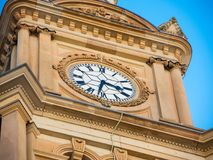Sand stone Clock tower with roman numeral clock in close up. A Sand stone Clock tower with roman numeral clock in close up royalty free stock images