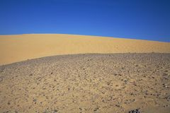 Sand and stone dunes under a blue sky Royalty Free Stock Photo