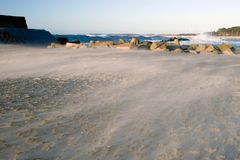 Sand storm on a beach. Strong wind making the sand fly low over the ground. Waves on water at the top. The Baltic Sea Royalty Free Stock Photos