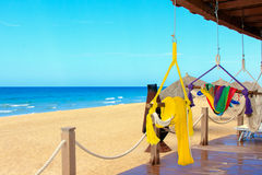 Sand sun ocean and hammocks. Beachfront view of a mexican resort with colorful hammocks and straw huts Stock Images