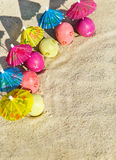 Sand texture (background) with colorful easter eggs with umbrellas on the beach. Stock Photos