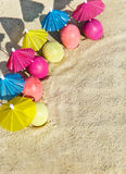 Sand texture (background) with colorful easter eggs with umbrellas on the beach. Royalty Free Stock Photo