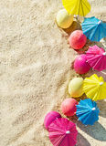 Sand texture (background) with colorful easter eggs with umbrellas on the beach. Stock Image
