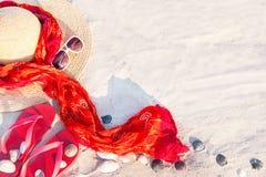 Sand texture with flip flop sandals, hat, pareos, sunglasses. Stock Photo