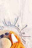 Sand texture with hat, towel, sunscreen and sunglasses on the a beach. Stock Images