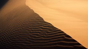 Sand texture with light and shadows in Erg Chigaga. Sand texture with light and shadows and wind-created waves in Erg Chigaga, Morocco Stock Images