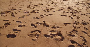 Sand texture. Marks of feet in the sand stock footage