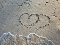 On the sand, there are two hearts drawing. Below is a bubble waves are coming to a little space, summer concept. Valentine concept royalty free stock images