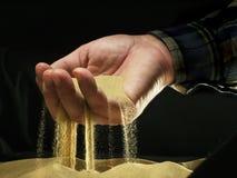 Sand till och med fingrar Arkivbild