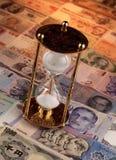 Sand-Timer auf Anmerkungen der ausländischen Währungen Lizenzfreie Stockfotografie