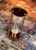 Sand timer on foreign currencies notes Royalty Free Stock Photography