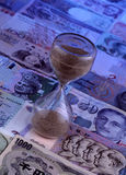 Sand Timer on Foreign currencies notes Stock Photography