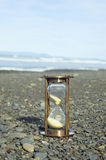 Sand Timer on Pebble Beach Stock Photos