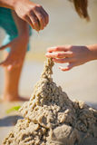 Sand tower. Children's game - construction from sand on the bank of a reservoir, the river or the sea. Handwork Royalty Free Stock Image