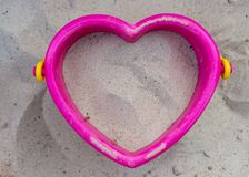 Sand toy - bucket with sand. Sand toy - bucket in the shape of a heart filled with sand royalty free stock images