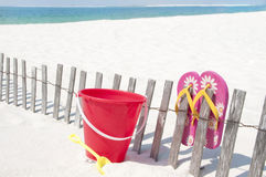 Sand toy and sandals at beach Stock Image