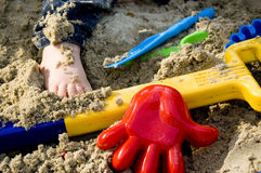 Sand Toys. A little bare child's foot buried in a sand box surrounded by colorful plastic toys Stock Photo