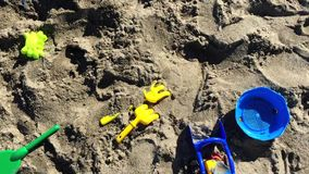 Sand toys scattered on the beach. Top view of scattered toys lying on the beach stock video