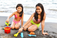 Sand Toys. Two little sisters playing on the beach with sand toys royalty free stock photo