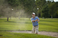 Sand Trap. A male golfer takes a swing at his ball in a sand trap and creates a big spray of sand Royalty Free Stock Photography