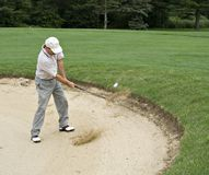 Sand Trap. Sand and ball can be seen flying as golfer hits from sand trap.l royalty free stock photo