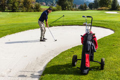 Sand trap hazard. A golf player playing from a sand bunker on a beautiful golf course stock photos