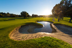 Sand trap nearly full of water near green Stock Image