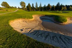 Sand trap nearly full of water near green Stock Photography