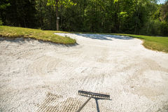 Sand trap, rake in a golf course sand bunkers, raking the sand Stock Photography