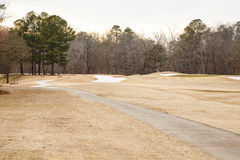 Sand Traps in Winter Golf Course. Sand traps beyond fairway on golf course in winter with brown grass Royalty Free Stock Photography