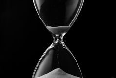 Sand trickling through the bulbs of an hourglass. Or egg timer measuring the passage of time on a dark background Stock Photos