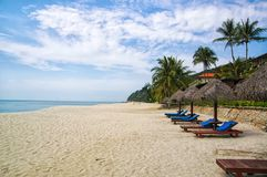 Sand tropic palms and sunbeds. Best Kuantan beach resorts. Luxury vacation at crystal clear waters and pristine beaches. Beach resorts rank as some of best in royalty free stock image