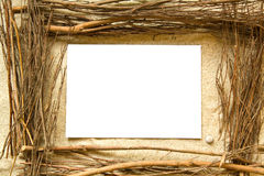 Sand and twigs frame. White empty card in the center of a frame of dry twigs lying on white sand Stock Photos