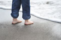 Sand under foot. Little boy standing near the beach wash Royalty Free Stock Photos