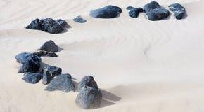 Sand with volcanic stones stock photo