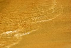 Sand and water. Sand and waves on the coastline Stock Photos