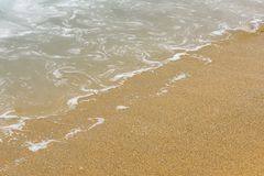 Sand and water. Wave of blue ocean on sandy beach Stock Photo