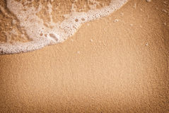 Sand with wave. Closeup of sand and small wave Stock Photography