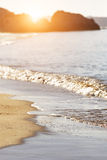Sand and wave background at sunrise Stock Photos