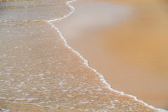 Sand and wave Stock Images