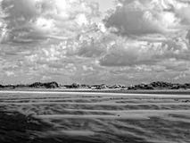 Sand waves in dune landscape by dramatic sky. Dune landscape by a strong sea breeze and dramatic sky at low tide, North Sea, Netherlands. Wind turbines in the Royalty Free Stock Images