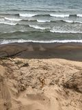 White foamy waves and sand at beach from lake. Sand and waves from Lake Michigan at Indiana Dunes State Park Stock Photo